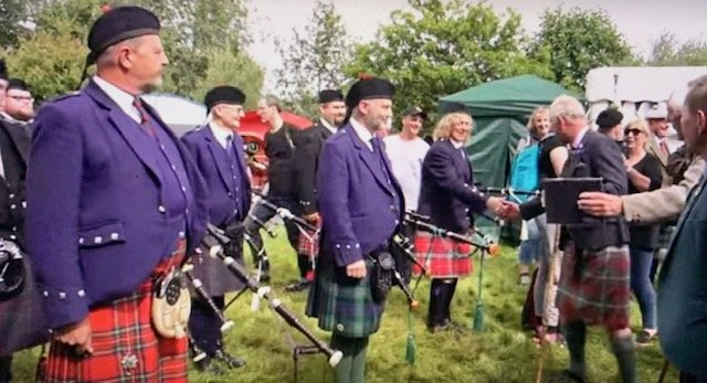 Prince Charles shakes pipers' hands